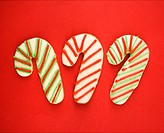 Three candy cane sugar cookies with decorative icing.