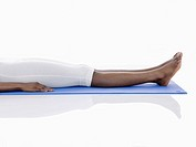 Young woman lying on exercise mat low section (thumbnail)