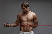 Mid adult man weight training with cable (thumbnail)