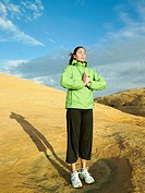 Woman meditating on rocky hill