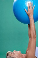 Mature woman exercising with Swiss ball