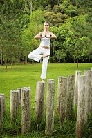 Woman doing yoga on tree stump