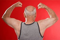 Senior man flexing muscles rear view