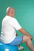 Senior man exercising on Swiss ball rear view