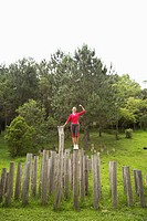 Woman balancing on stump and flexing muscles