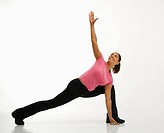 Mid adult multiethnic woman wearing exercise clothing holding yoga pose and smiling.