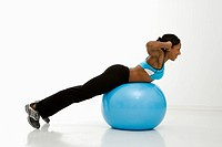 Profile of African American young adult woman working out with exercise ball