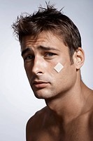 Mid adult man with adhesive plaster on cheek (thumbnail)