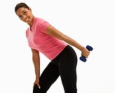 Mid adult multiethnic woman exercising with dumbbell smiling and looking at viewer