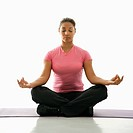 Mid adult multiethnic woman sitting in lotus position on exercise mat with eyes closed and legs crossed