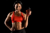 Smiling African American young adult woman holding water bottle with hand on hip