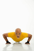 Mid adult multiethnic man wearing yellow exercise shirt doing pushups while looking at viewer