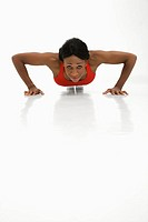African American young adult woman doing push up and looking at viewer