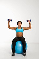 African American young adult woman sitting on exercise ball and raising dumbbells over head.