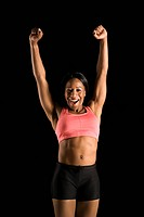Smiling African American young adult woman in athletic apparel stretching arms above head