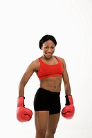 African American young adult woman wearing boxing goves smiling at viewer
