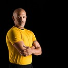 Mid adult multiethnic man wearing yellow exercise shirt with arms crossed looking at viewer