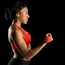 Profile of African American young adult woman lifting dumbbell.