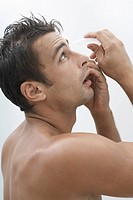 Mid adult man putting in eye drops