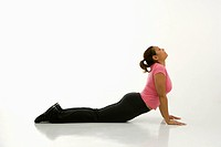 Side view of mid adult multiethnic woman wearing exercise clothing holding cobra yoga pose