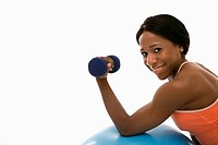 African American young adult woman leaning on exercise ball holding dumbbell and smiling at viewer
