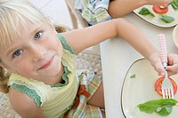 Portrait of girl eating salad, smiling and looking up