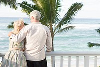 Senior couple at seaside, man putting arm around woman's shoulder