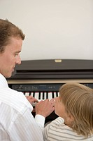 Father and son playing piano, Rear View, Differential Focus