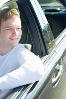 Man smiling and sitting in car, looking outside from the window