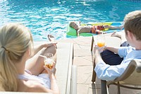 Parents on reclining chairs looking at son lying on pool raft