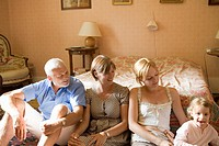 Caucasian family sitting by the bed, Front View