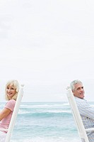 Portrait of senior couple sitting on chair on beach, smiling and looking at camera, copy space