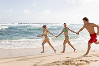 Young Women and Young Man Running on Beach Hand in Hand