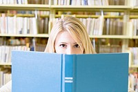 College Girl Peeking from behind Book, Looking at Camera