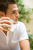 Caucasian man drinking a cup of tea, Side View, Differential Focus