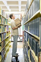 College Boy Standing on Stool and Holding Books