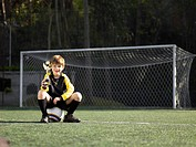 Boy sitting on soccer ball and holding trophy portrait