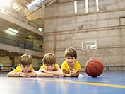 Boys lying on floor near basketball portrait