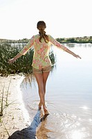 Young woman walking in lake with arms outstretched