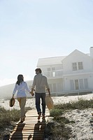 Couple walking towards house on beach (thumbnail)