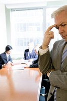 Businessman Contemplating in a Meeting, Focus on Foreground