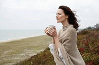 Young woman drinking coffee at beach (thumbnail)