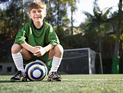 Boy sitting on soccer ball portrait, low angle view (thumbnail)