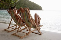 Mid adult couple on lounge chairs on beach, St. John, US Virgin Islands, USA (thumbnail)