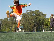 Boy kicking in soccer field