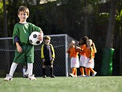 Boy holding soccer ball, children in soccer uniforms in background portrait