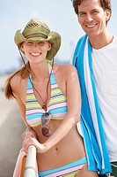 Young couple in beach attire by railings portrait
