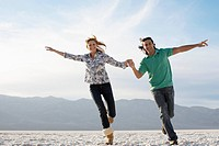 Couple running with arms outstretched