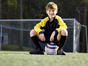 Young boy sitting on soccer ball portrait, low angle view