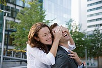 Woman surprising man from behind